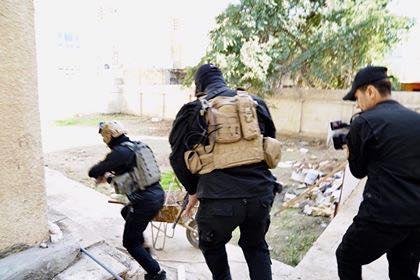 """صور: أسلحة وعشرات الباجات في مقر فصيل مسلح """"وهمي"""" بمنطقة الكرادة"""