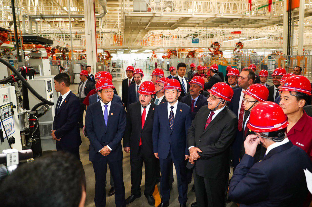 """ظهر بخوذة """"حمراء"""".. عبد المهدي """"معجب"""" بمعمل صيني لصناعة السيارات (صور)"""