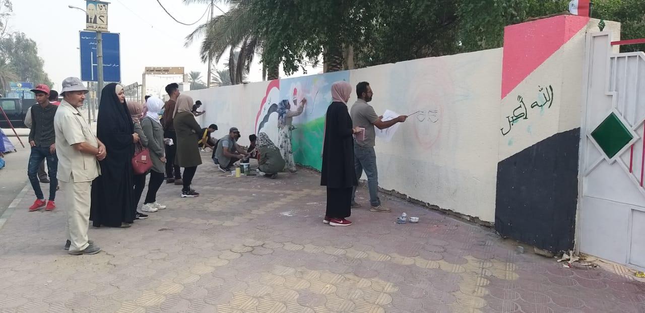 """فتيات وشبان يلونون جدران """"شارع الاعتصامات"""" في السماوة (صور)"""
