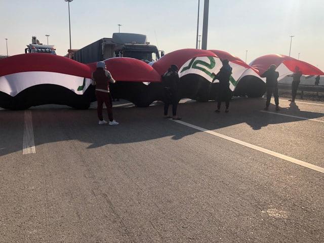 باستخدام علم عراقي كبير ..  محتجو الديوانية يغلقون طرقاً رئيسة (فيديو وصور)